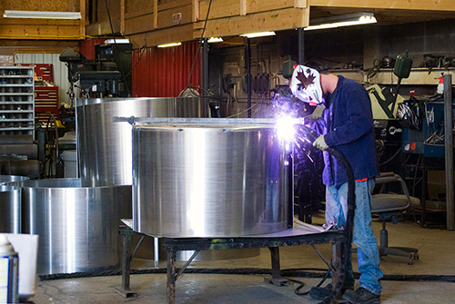 A worker welding a sprayer tank in our fabrication facility.